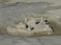 Cute sand castle on the beach across from the lighthouse